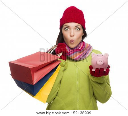 Concerned Expressive Mixed Race Woman Wearing Winter Clothes Holding Shopping Bags and Piggy Bank Isolated on White Background.