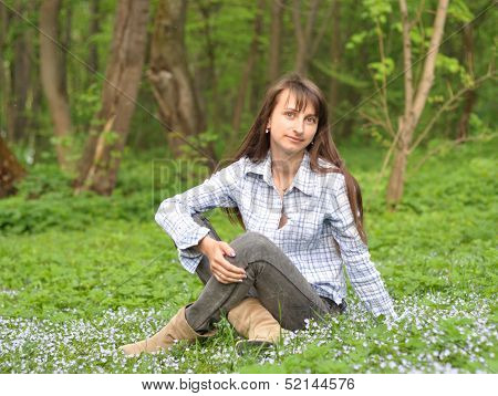 Beautiful Smiling Young Woman Sitting On The Grass In The Park