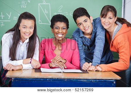 Portrait of happy young teacher with teenage students at desk in classroom