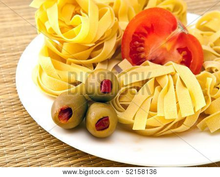 Italian fettuccine nest pasta with olives and tomat on a plate