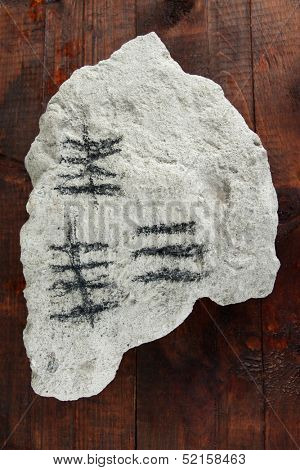 Counting days by drawing sticks on stone on wooden background
