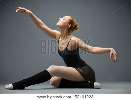 Dancing on the floor ballerina with outstretched arms, isolated on grey. Concept of elegant art and sportive hobby