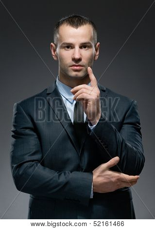 Portrait of making attention gesture man wears business suit and black tie