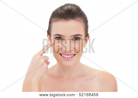 Content natural brown haired model touching her cheekbone on white background
