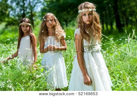Three Girls Wearing White Dresses In Woods.