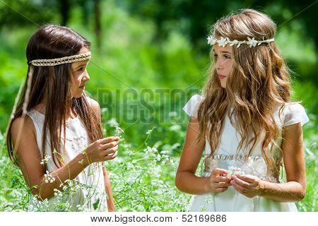 Two Girls Standing In Flower Field.