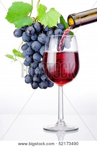 Pouring A Glass Of Red Wine And Bunch Of Grapes With Leaves Isolated On White Background
