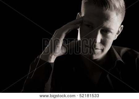 Low-key portrait of young charming man with hand at temple looking aside, black and white, isolated on black background.