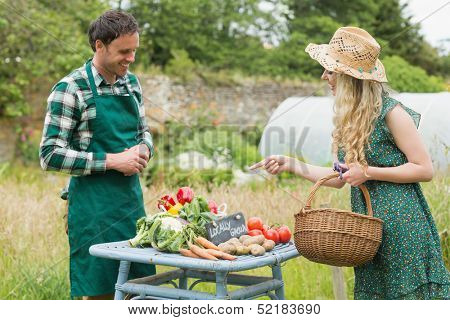 Beautiful blonde woman buying vegetables at farmers market from a handsome farmer
