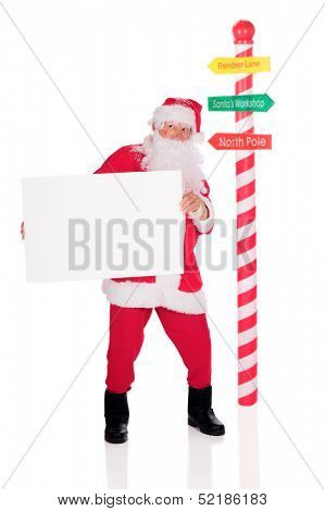Santa Claus standing by a candy striped pole while holding a blank sign.  On a white background.