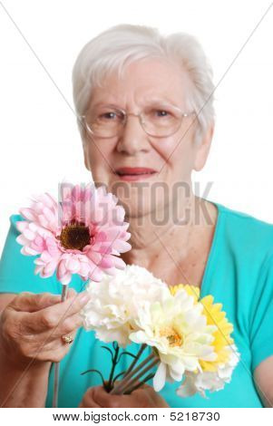 Happy Senior Woman Offering A Fake Daisy Focus On Flower