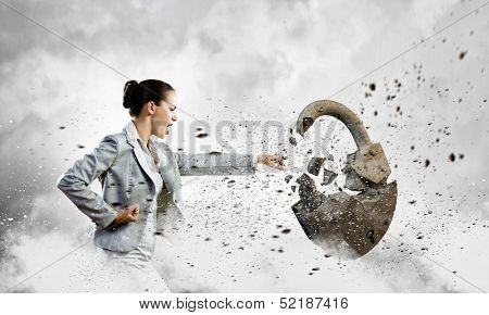 Image of businesswoman crashing lock with hand