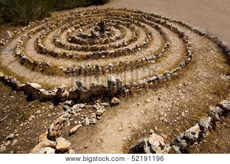 Atlantis spiral sign in Ibiza with stones on soil at Balearic Islands