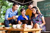 stock photo of internet-cafe  - Asian friends or colleagues enjoying leisure time in a cafe - JPG