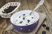 stock photo of porridge  - Rice porridge with raisins in a bowl on the table - JPG