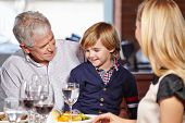 Family with smiling grandfather and his grandchild eating out in a restaurant