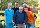 stock photo of rollator  - Family visiting grandfather at the nursing home helping him with the walker - JPG