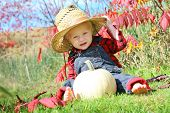 picture of baby cowboy  - a cute baby boy is sitting outside in the grass with a white pumpkin on a sunny autumn day wearing a straw hat flannel and overalls like a little farmer - JPG