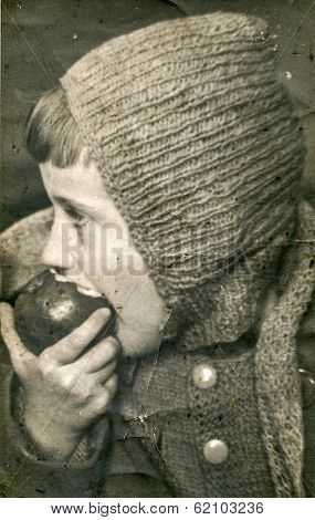 LODZ, POLAND, CIRCA 1970's: Vintage photo of little boy eating an apple