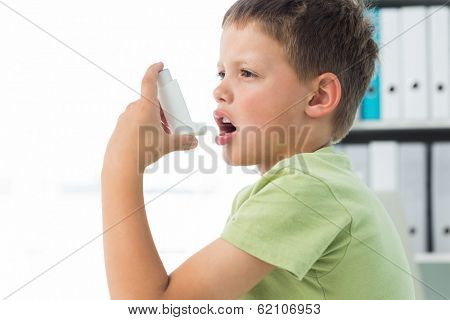 Side view of little boy using an asthma inhaler in clinic