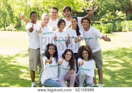 Portrait of confident young volunteers raising thumbs up in park