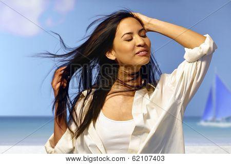 Beautiful young woman enjoying summer sun on the beach eyes closed.