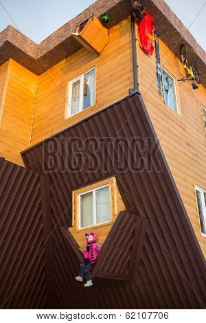 Little girl sitting on the roof of the upside-down house