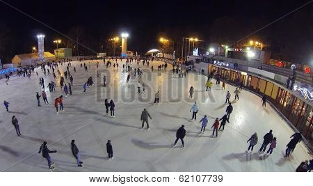 Many people skate on big rink in winter night. Aerial view