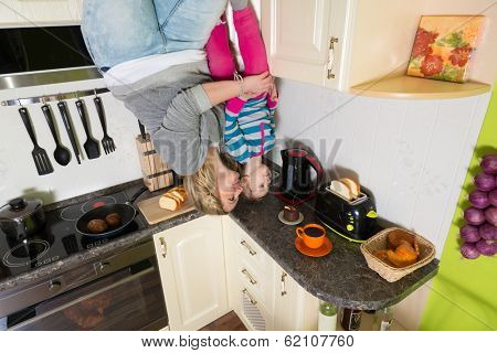 Mother with daughter stand upside down in the kitchen with toaster