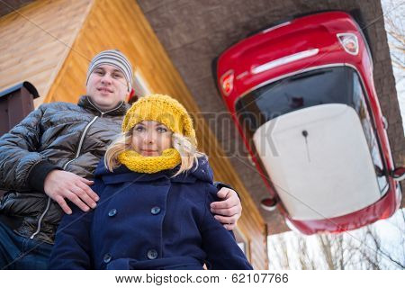 Couple against the inverted house with red car