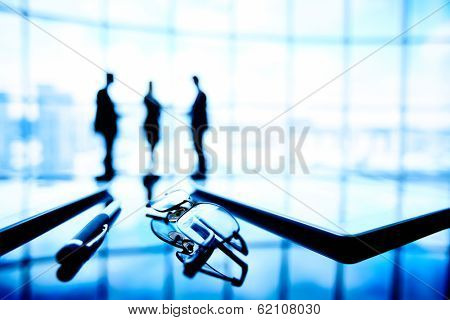 Image of eyeglasses, touchpads and pen at workplace with businesspeople on the background