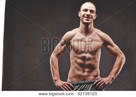 Image of topless muscular man posing in the darkness