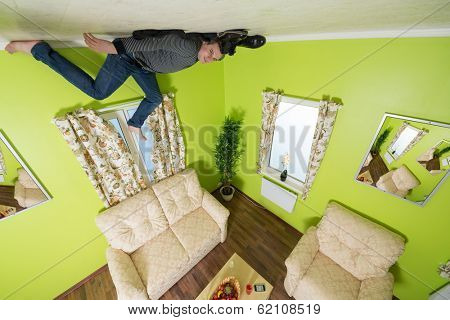 Man in jeans lying on the ceiling under the sofa without shoes and socks