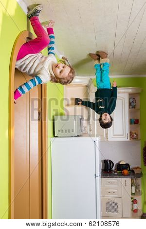 Two children upside down on the ceiling of kitchen at inverted house