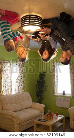 Family of four sits on the ceiling upside down with candles at inverted house