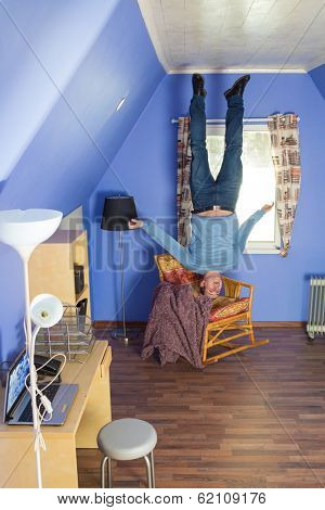 Man in jeans standing upside down under the armchair
