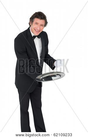 Portrait of smiling waiter showing empty tray over white background