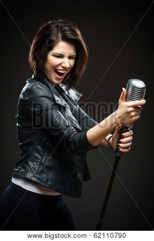 Half-length portrait of female rock singer wearing black jacket and handing mic on grey background. Concept of music and rave