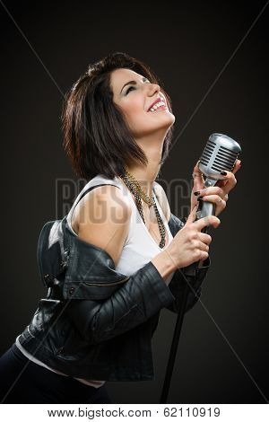 Half-length portrait of female rock singer wearing black jacket and handing mike on grey background. Concept of music and rave