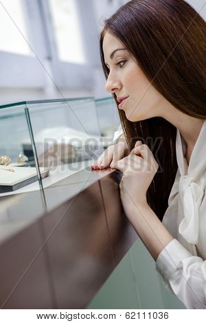 Close up of girl looking at jewelry in window case at jeweler's shop. Concept of wealth and luxurious life