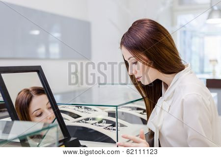 Girl choosing jewelry at jeweler's shop. Concept of wealth and luxurious life