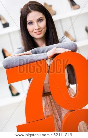 Woman showing the percentage of sales on stylish pumps in the shopping center against the window case with pumps