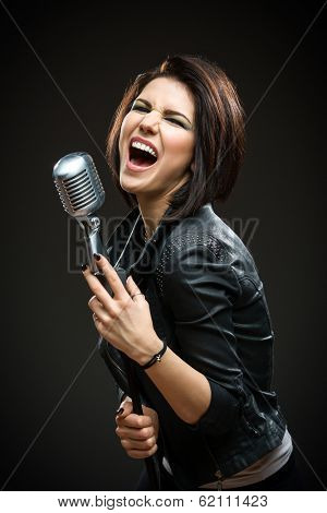Half-length portrait of female rock musician wearing black jacket and keeping mike on grey background. Concept of music and rave