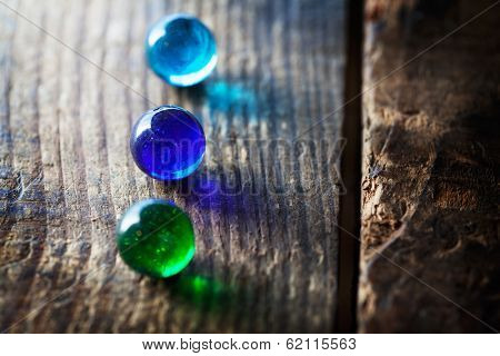 blue and green glass marbles on a grungy wooden surface.