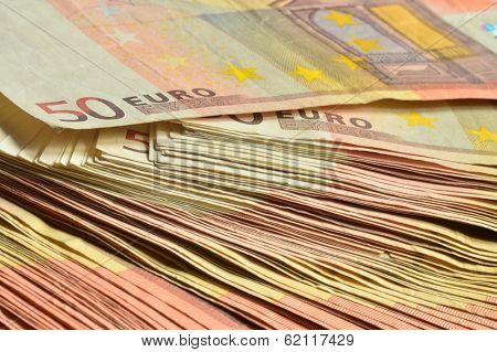 Few thousands euro in fifty euro banknotes stacked together as financial background.