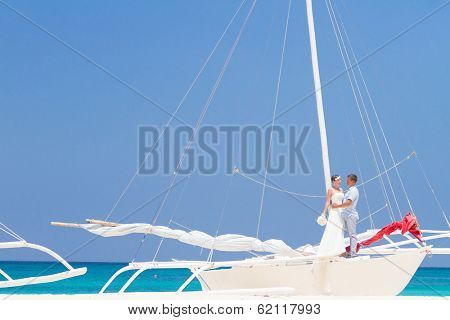 young happy couple, bride and groom, on wedding day ready for travel by sail boat