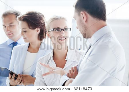 business concept - friendly businessman and businesswoman having discussion in office