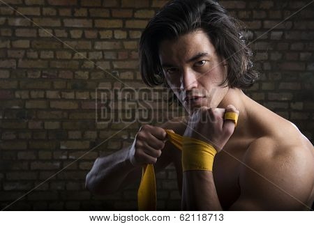 Bare chested young Malaysian boxer wrapping straps around hands