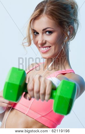 Smiling athletic woman pumping up muscules with dumbbells on gray background