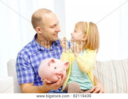 family, children, money, investmen and happy people concept - happy father and daughter with big pink piggy bank